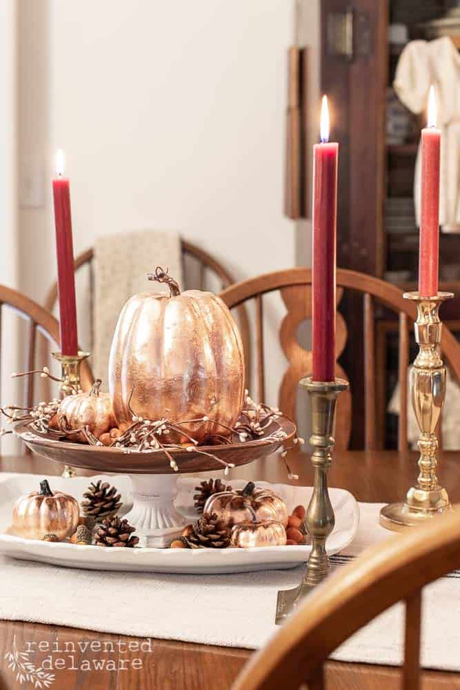copper leaf pumpkins sitting on dining table as a center piece with vintage brass candlesticks