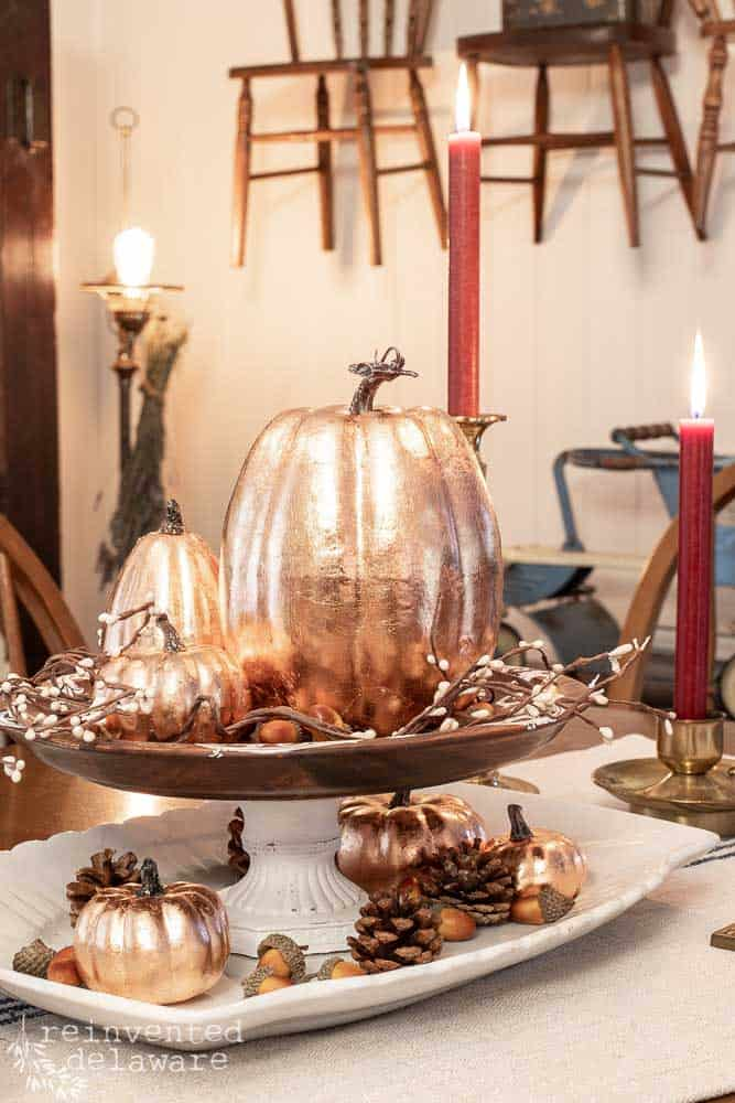 copper leaf pumpkins sitting on top of cake stand with faux pine cones and acorns sitting around them