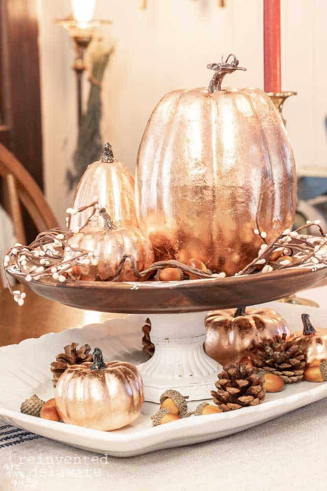 copper leaf pumpkins displayed on a cake stand with fall decorations
