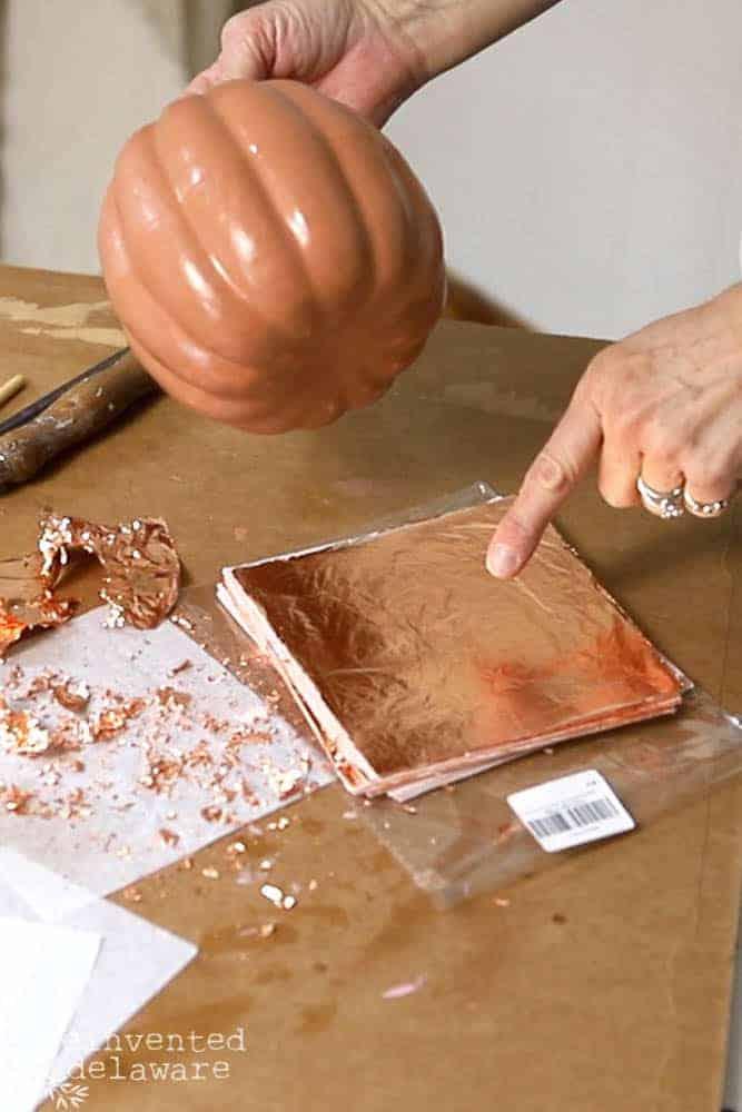 lady placing pumpkin on copper leaf sheet