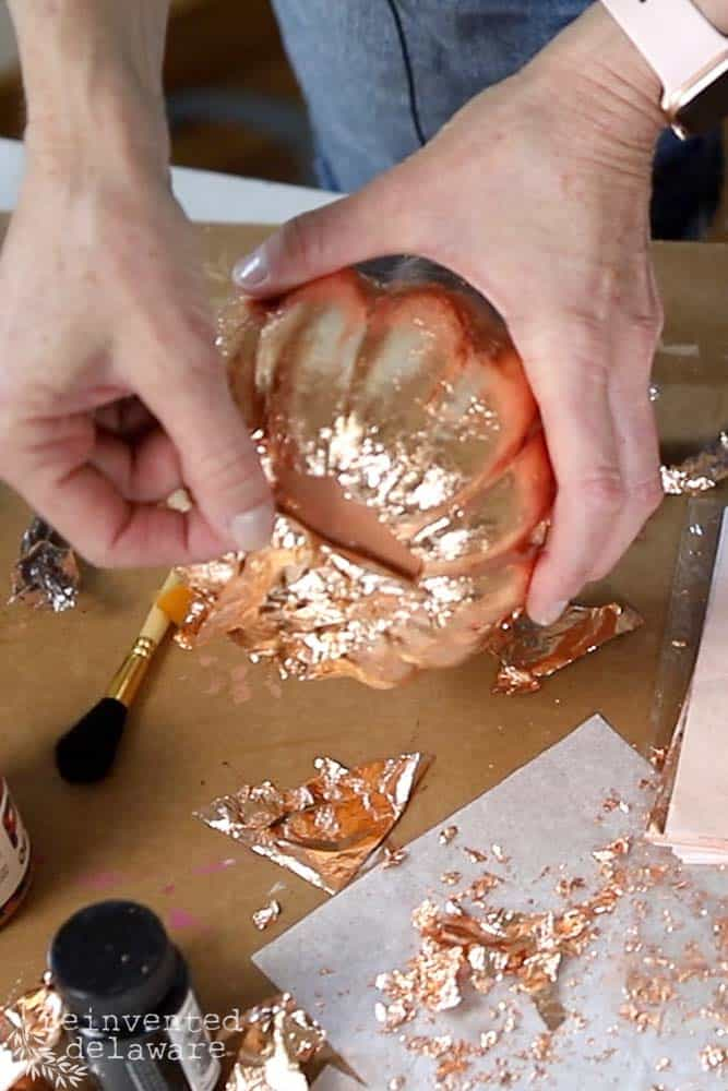 lady removing excess copper leaf from craft pumpkin