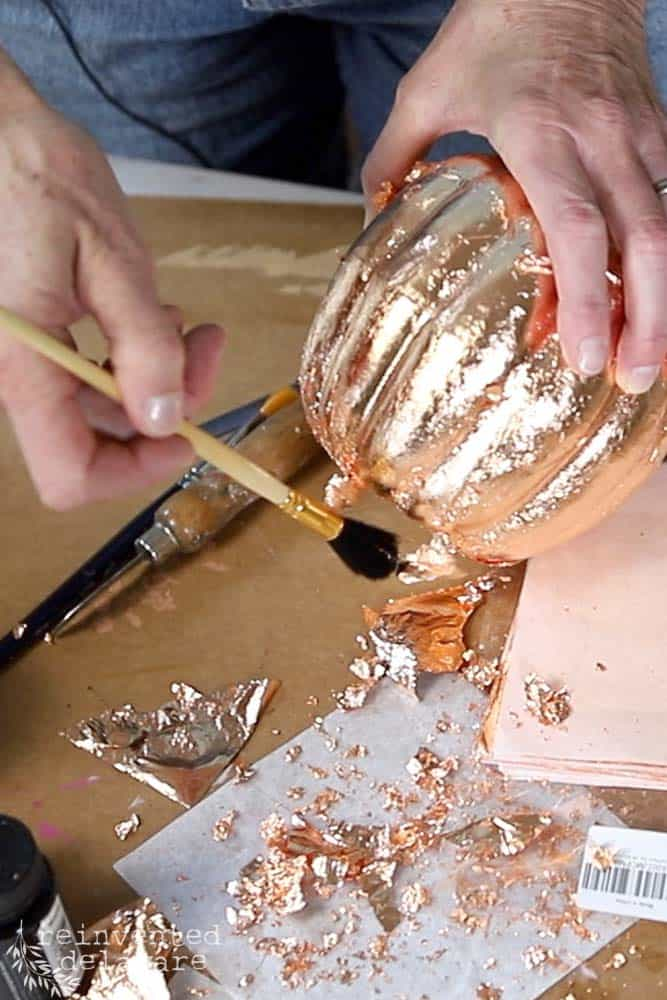 lady brushes off excess copper leaf on a pumpkin using a loose leafing brush