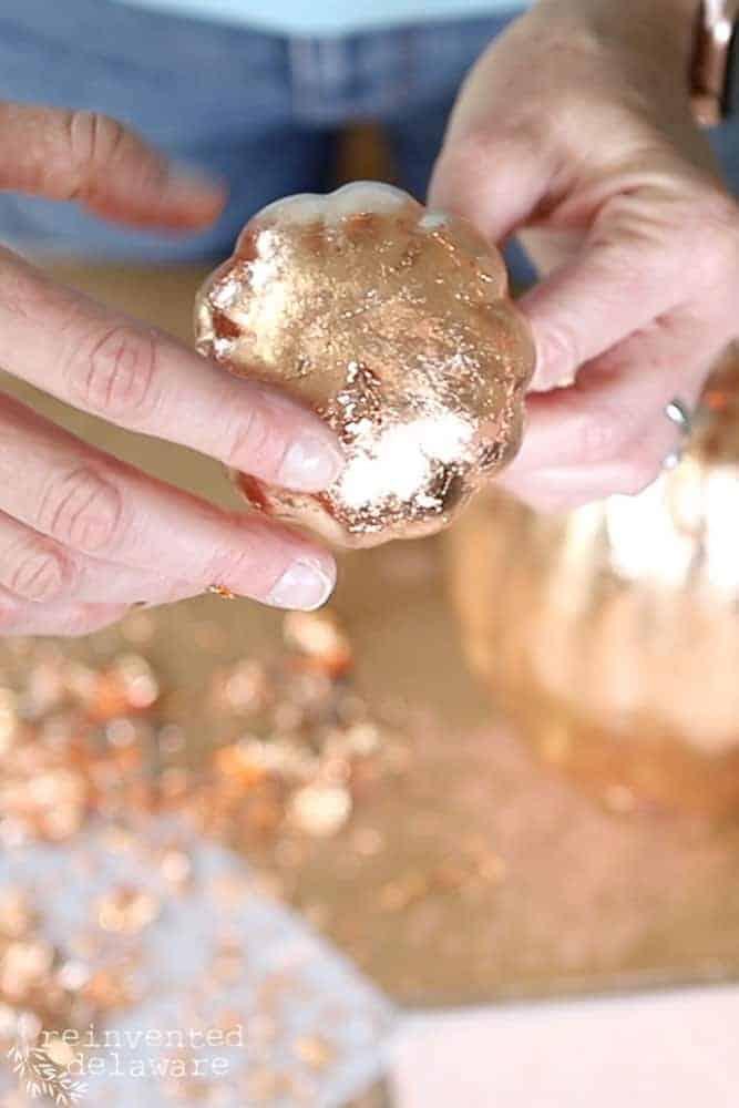 lady applying copper leaf to a craft pumpkin