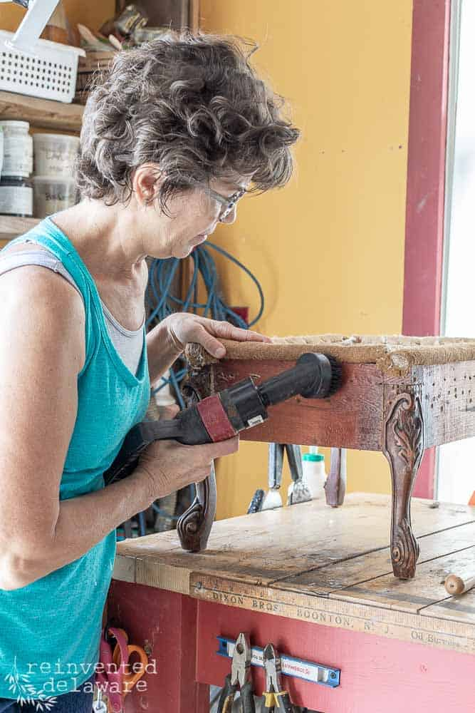 lady using shop vac in how to upholster a footstool blogpost