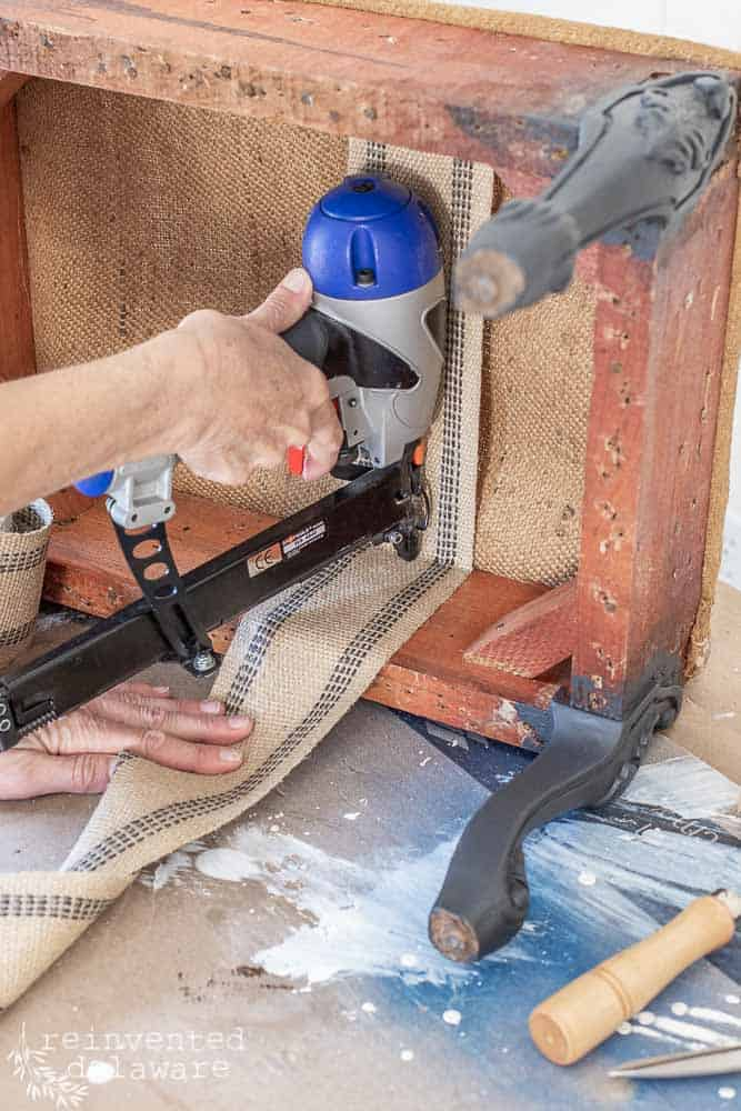 lady using a pneumatic staple gun to upholster a footstool