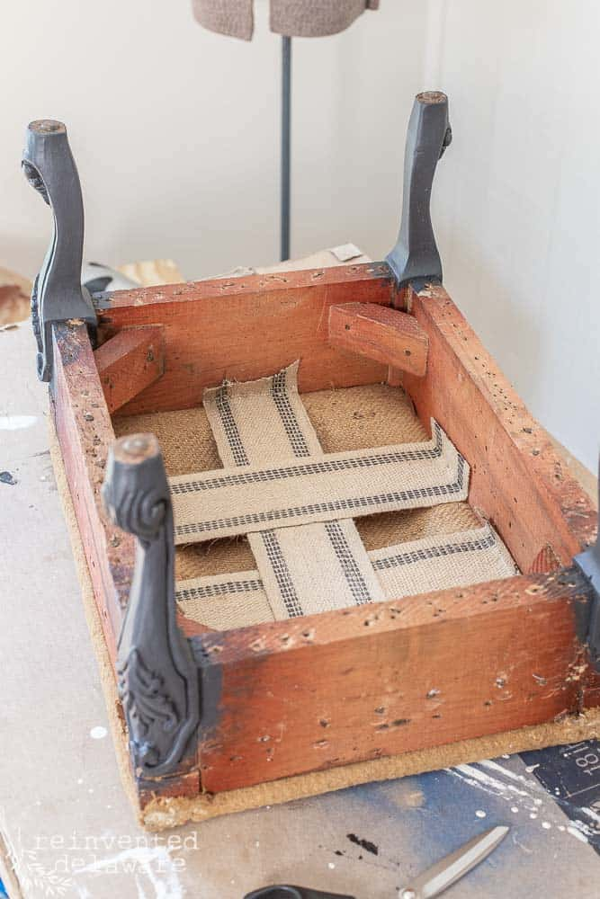upholstered footstool turned upside down to add new upholstery webbing