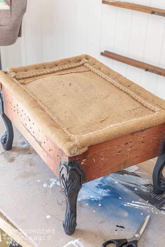 antique footstool with old fabric off and legs painted