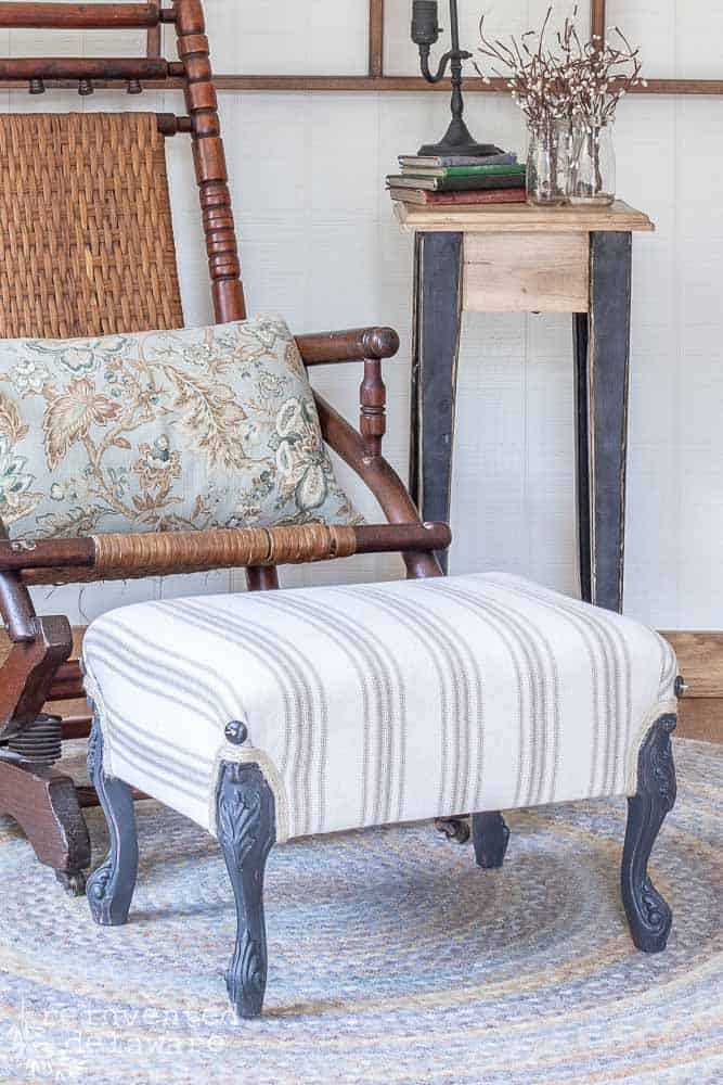 close up of finished farmhouse style upholstered footstoll for tutorial post on how to upholster a footstool
