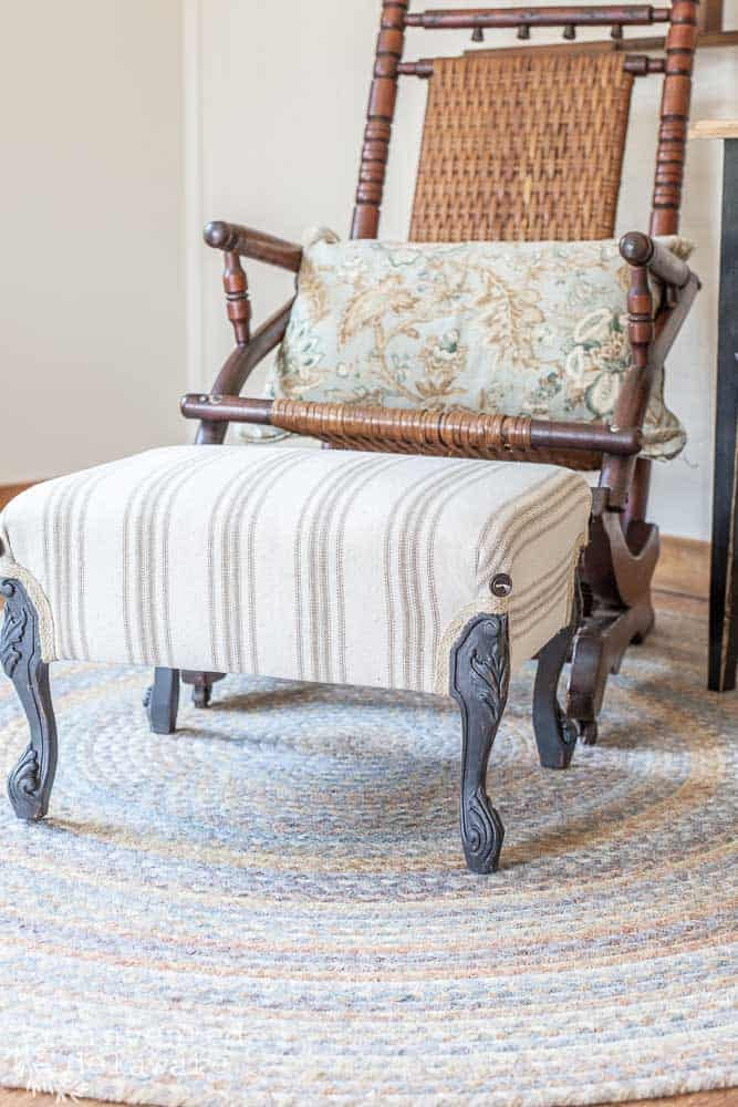 staged shot of antique upholstered footstool with a vintage rocker in background
