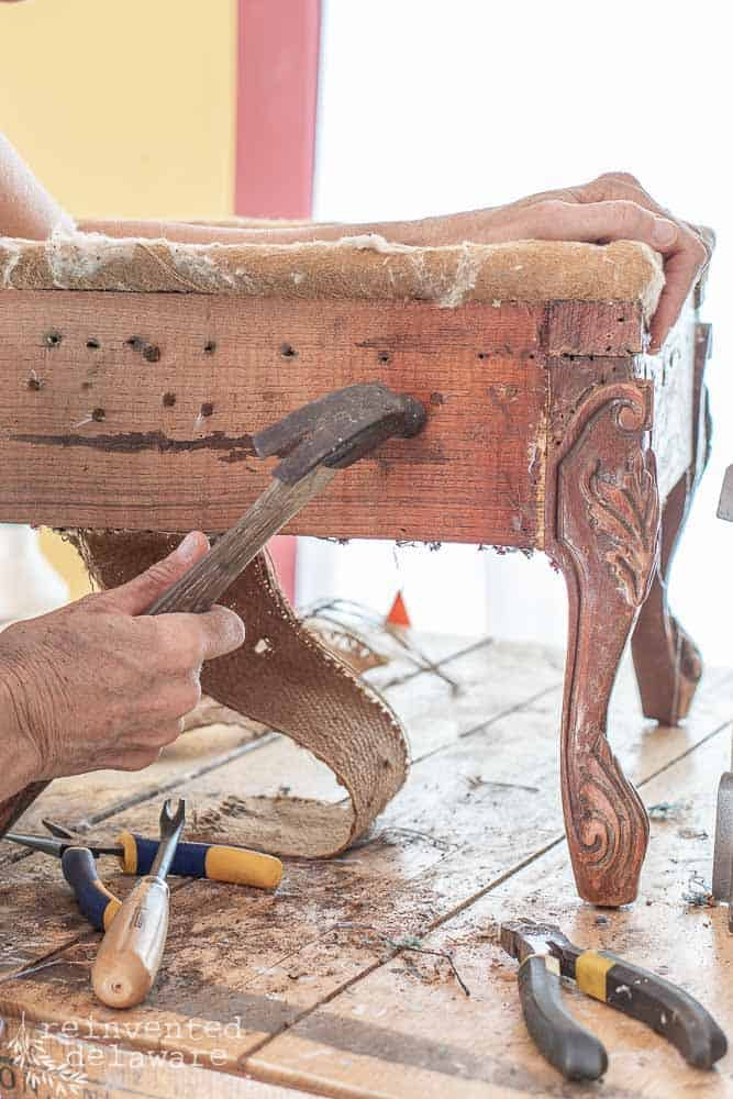 lady showing how to tap in rusted tacks in upholstery project