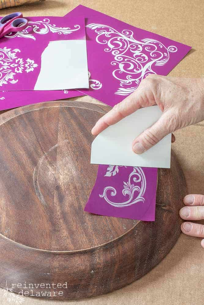 lady applying silk screen stencil to bottom of wooden cake plate