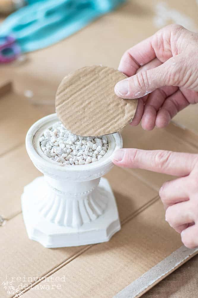 lady prepping plastic candle holder for thrift store home decor project