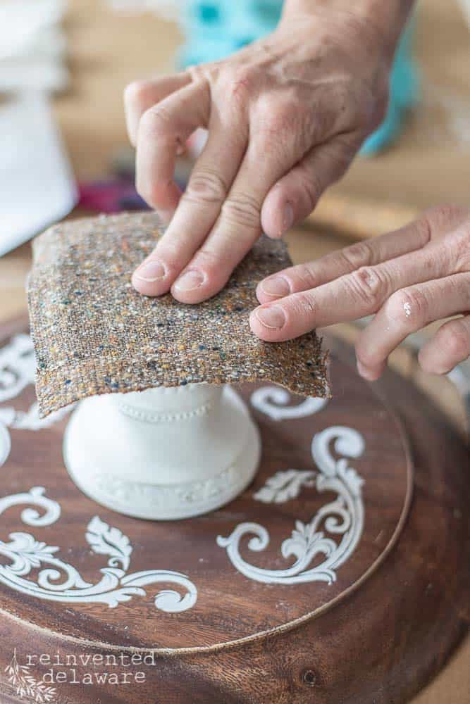 lady applying padding to base of candle stand