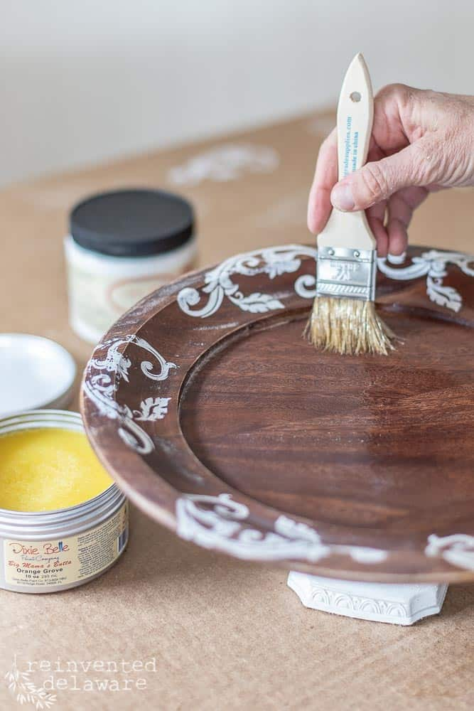 lady applying Dixie Belle Big Mama's Butta wax to wooden cake plate