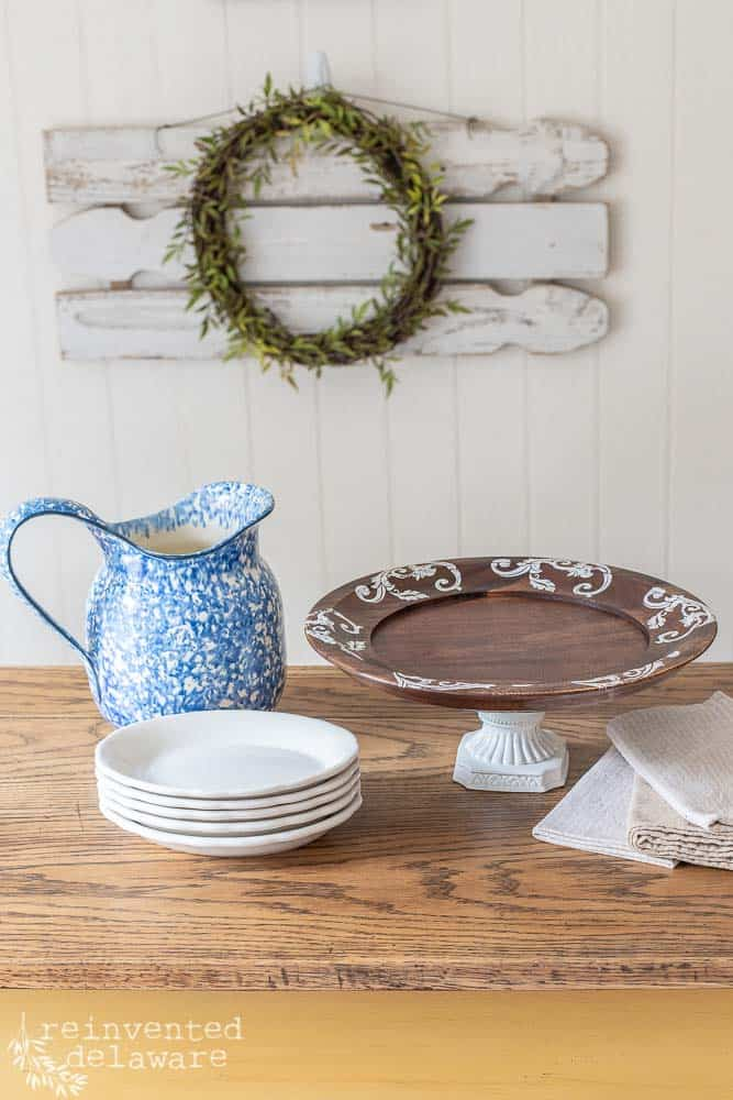 thrift store home decor cake stand staged with blue pitcher, stack of plates and napkins on a wood table with wreath hanging on wall in background