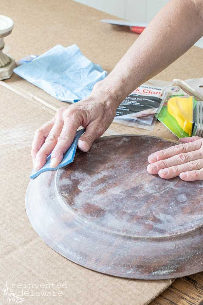 lady sanding wood cake plate to prep for painting