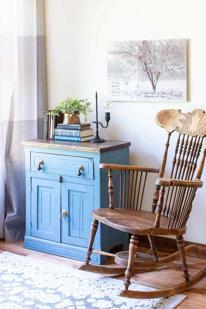 side view of staged washstand with vintage items sitting on top, wood rocker and wall decor