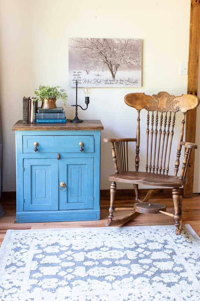front view of staged washstand with vintage items on top, rocker sitting beside and wall decor