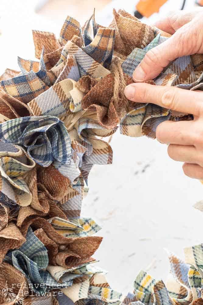 lady adding jute twine hanger to diy wool fabric wreath for fall