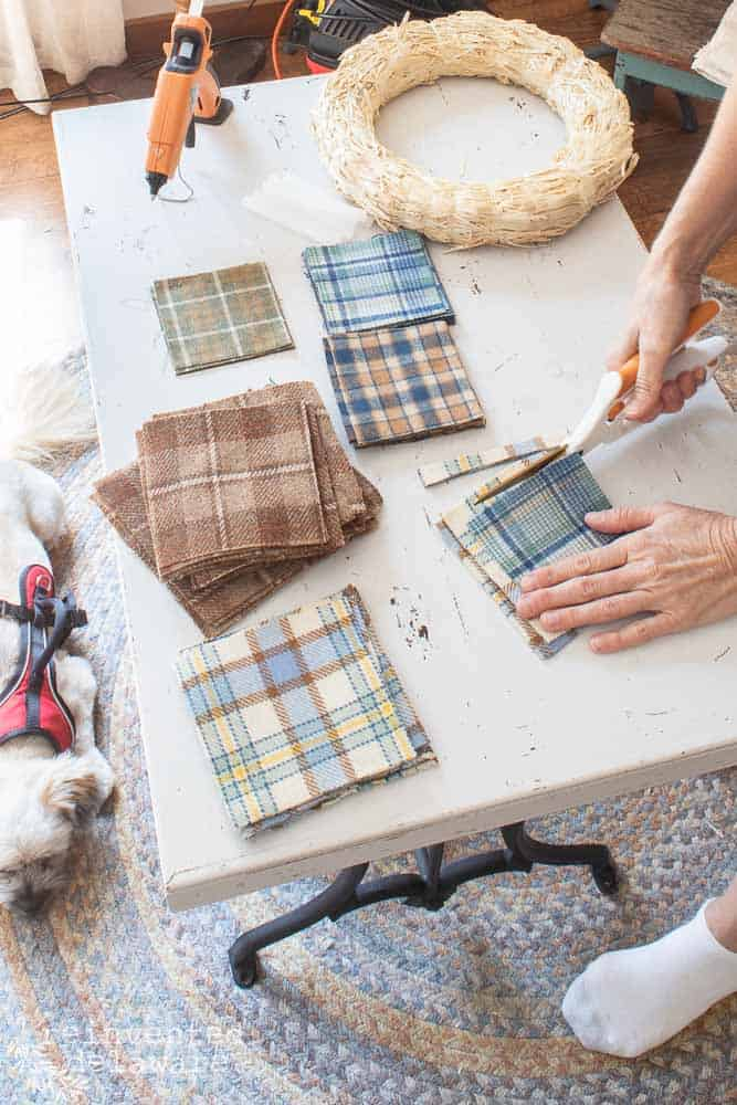 lady cutting squares of wool fabric for cheap wreaths for fall blog post tutorial