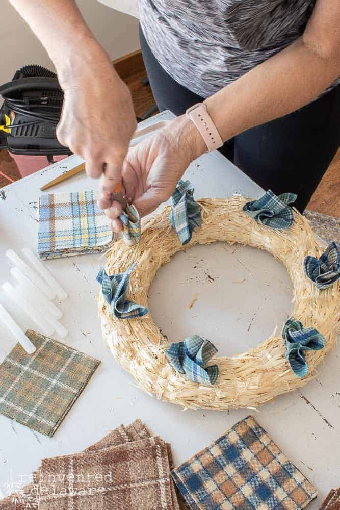 lady showing how to insert squares of fabric into straw wreath for diy fall wreath ideas