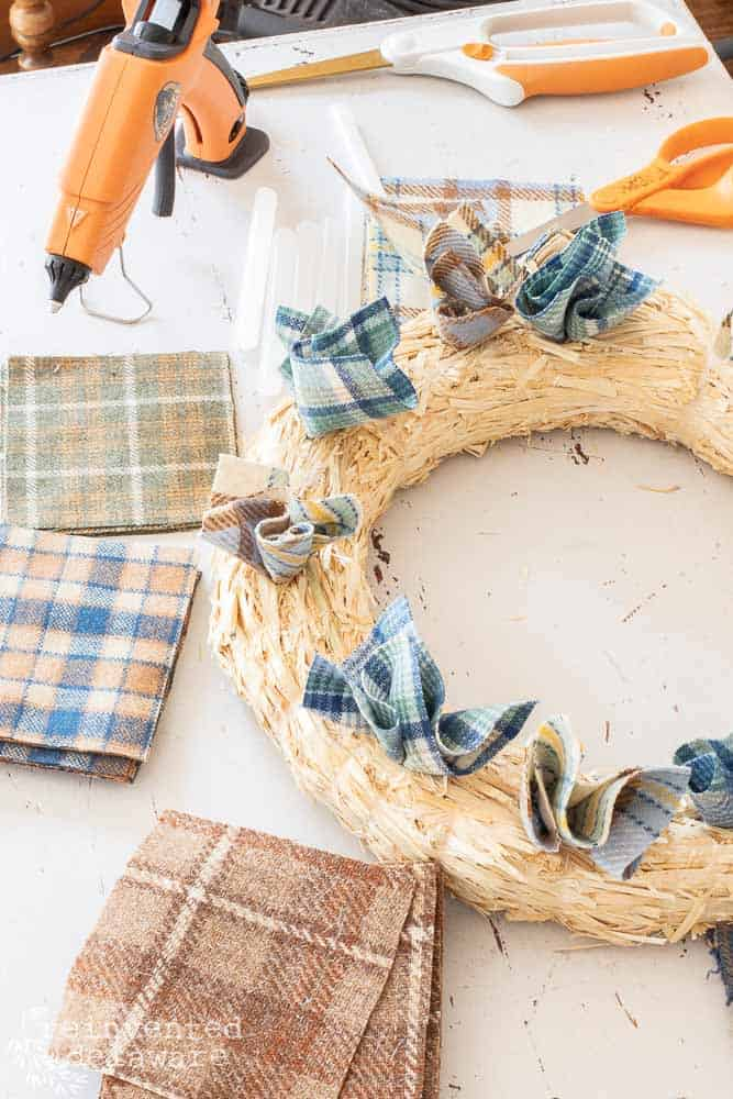 wool scraps of fabric already inserted into straw wreath for cheap wreaths for fall blog post
