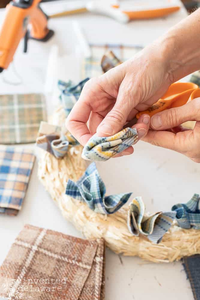 """lady showing how to use scissors with 3"""" wool scrap creating a pointed end to apply hot glue"""