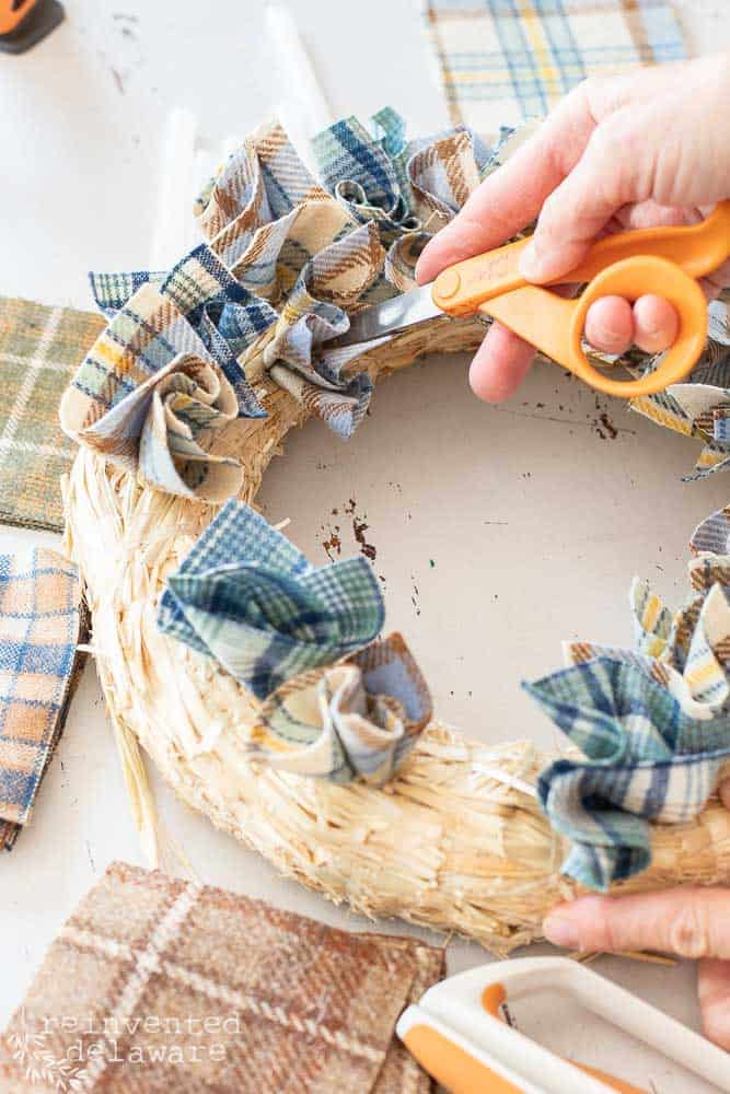 lady using blunt end of scissors to insert fabric squares into straw wreath for fall decor