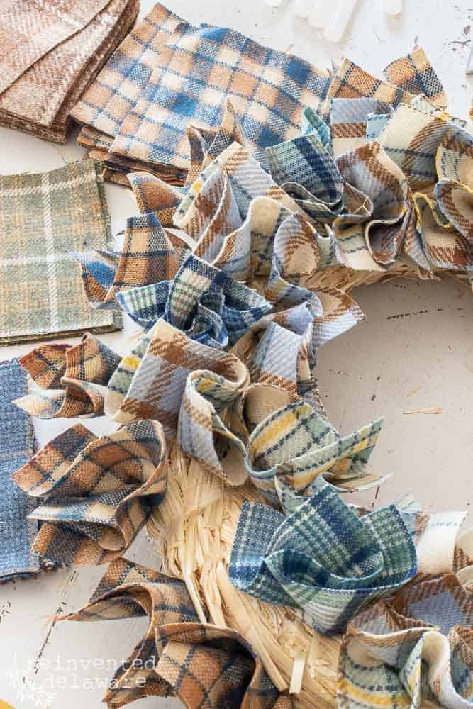 wool plaid wreath with many pieces of wool scrapes attached to straw wreath