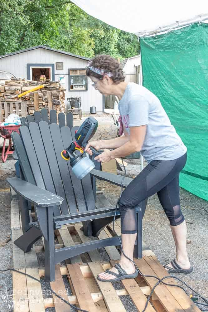 lady using Wagner Flexio 2000 power sprayer to spray paint an Adirondack chair