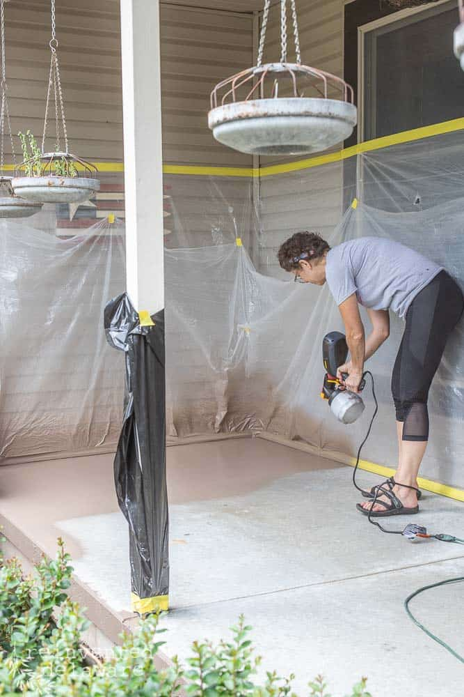 lady using the Wagner Flexio 2000 to spray paint a concrete front porch floor