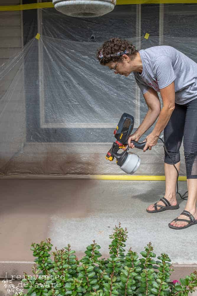 lady using Wagner Flexio 2000 paint sprayer to spray paint a concrete front porch floor