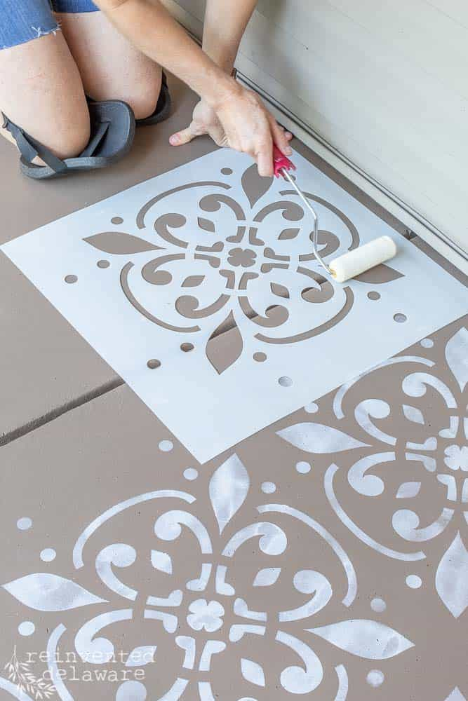 lady using paint foam roller and stencil to stencil the concrete front porch floor