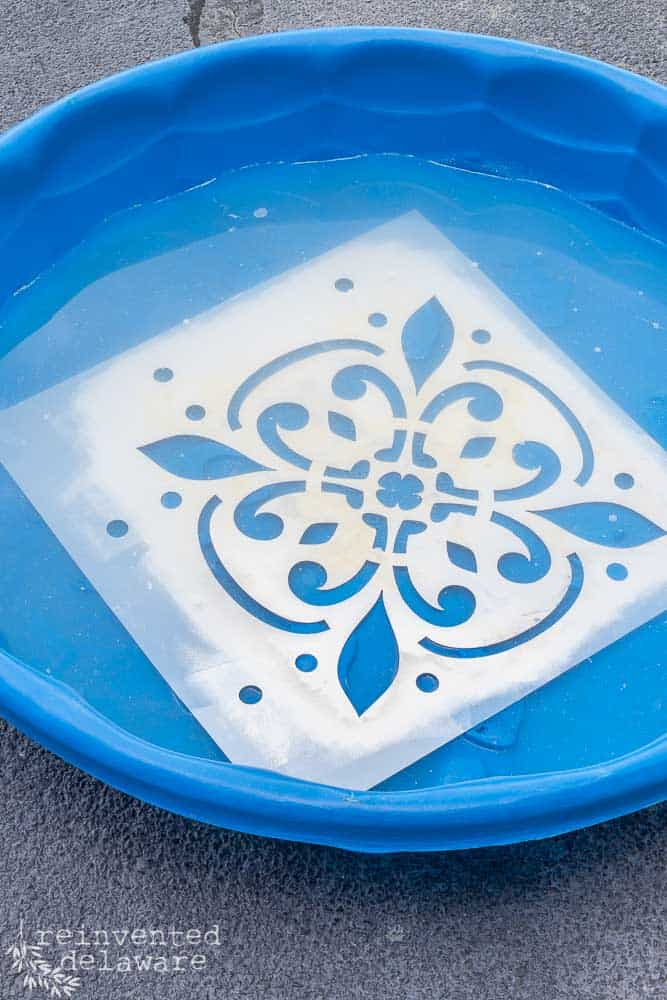 large floor stencil soaking in a childs small pool in order to clean off paint