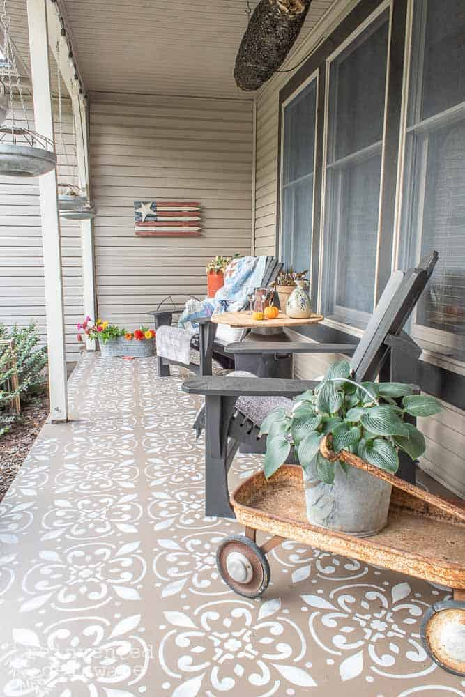 front porch after showing painted Adirondack chairs, various plants and various decor pieces