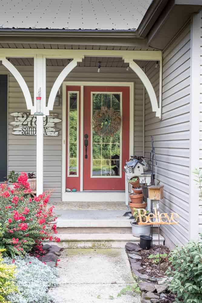 picture of a porch before makeover showing front door with a wreath and various porch decor items