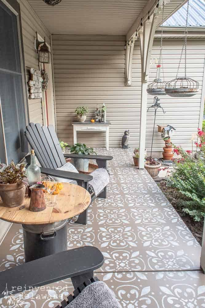 concrete front porch that has been painted and stenciled and showing two Adirondack chairs, various plants and home decor pieces