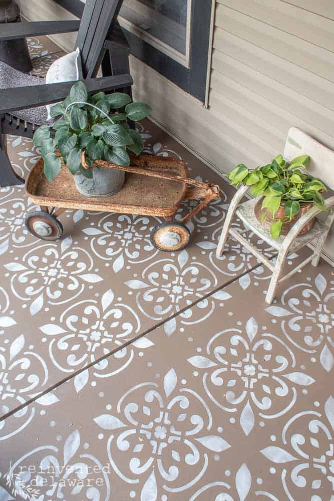 top view of painted and stenciled concrete floor on front porch showing two plant in vintage wagon and vintage childs chair