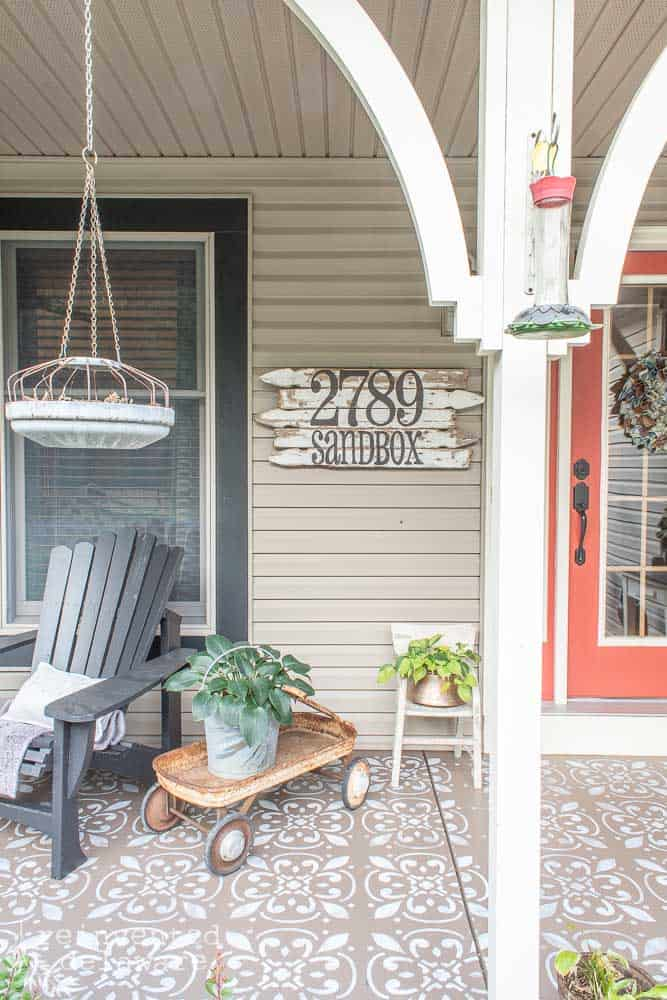 picture of front porch showing address sign made from picket fences, a rusty wagon with a plant, a child's chair with a plant, and an Adirondack chair that was painted with a Wagner Sprayer
