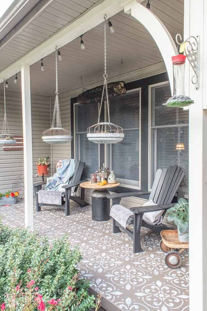 picture of the side view of a front porch makeover with the painted furniture, painted and stenciled floor and various plants and home decor pieces