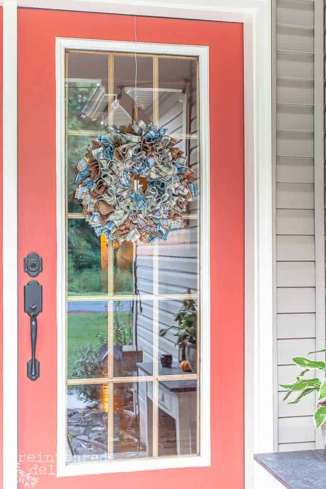red front door on a front porch with a cheap diy wool plaid wreath hanging on the door
