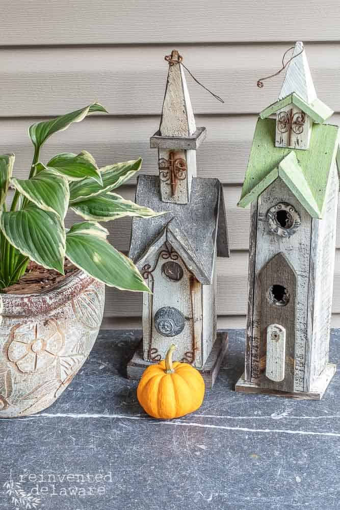 picture of home decor for a front porch with a small pumpkin sitting in front of two small church decor and a plant on the side