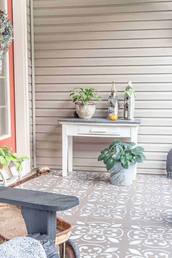picture of a small table with various home decor pieces and plants sitting on a front porch