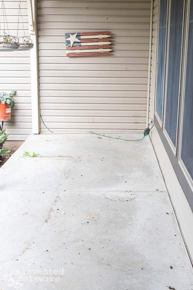 concrete front porch floor with all the decor and furniture removed and ready for makeover