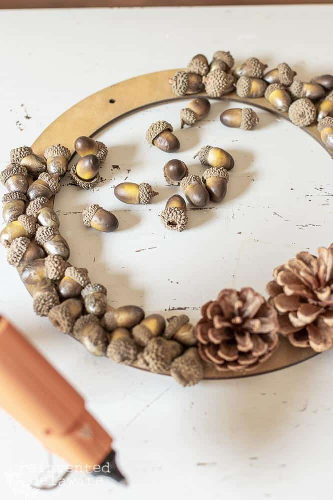pine cone wreath with acorns glued all the way around except for small area left open of the hanger to be attached.