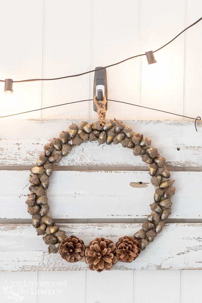 Finished DIY pine cone wreath with acorns hanging on a fence picket sign with a string of lights hanging above the wreath.