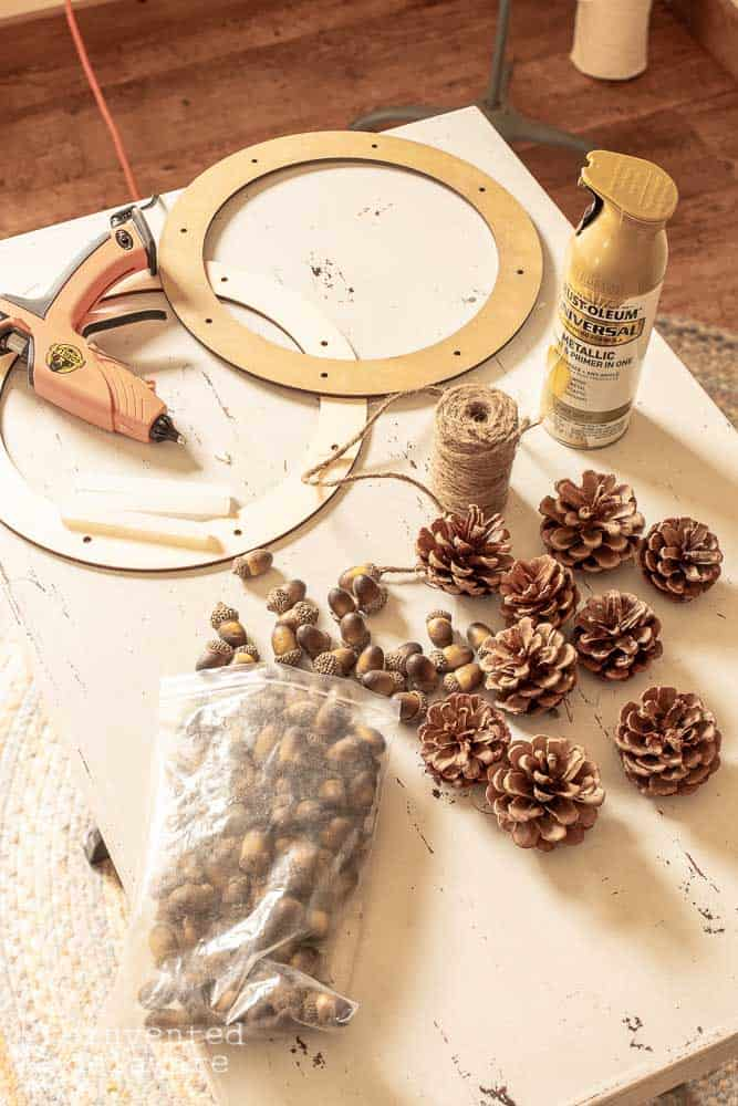 supplies for diy pine cone wreath with acorns wreath project laying on a table, pine cones, acorns, spray paint, wood wreath form, glue gun, spray paint, jute twine
