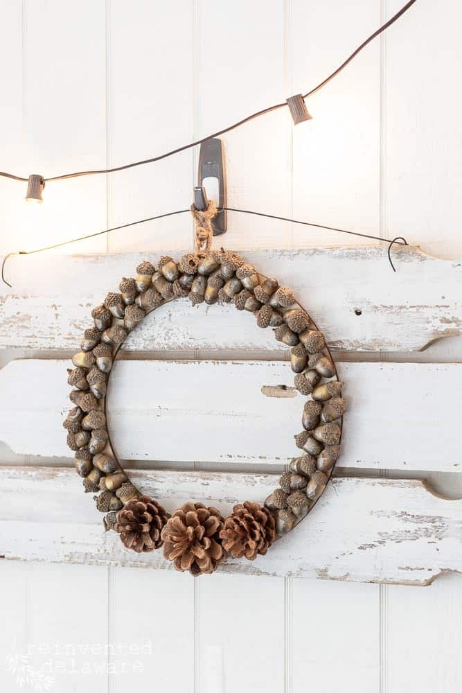 A side view of the pine cone and acorn fall wreath that is displayed on a picket fence wall sign with pation lights hanging above.