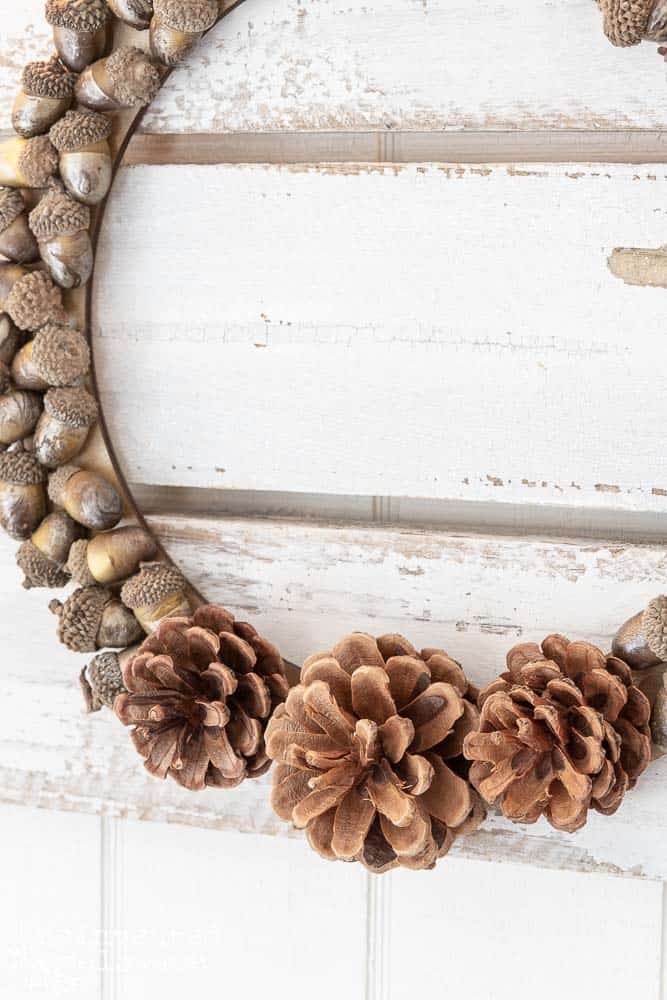 Side view and close-up shot of pine cones glued onto the wreath form with acorns glued all the way around the wreath form to create a fall wreath.