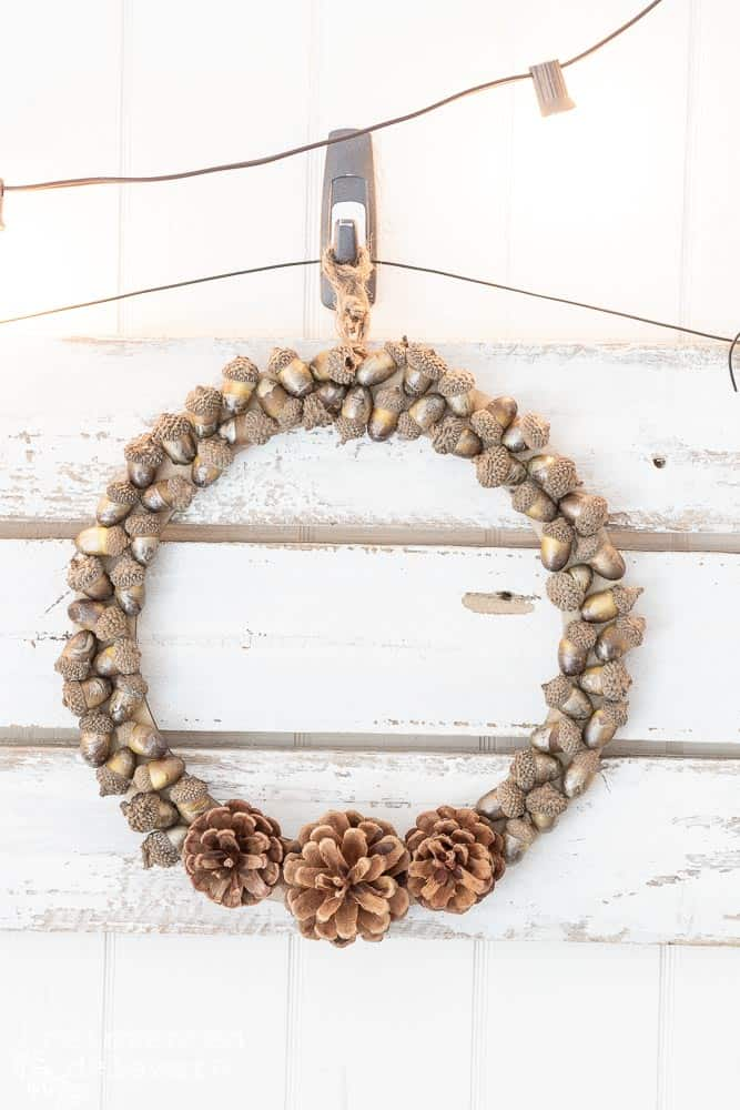 Full view of pine cone wreath with acorns glued onto a wood wreath frame and hanging on a picket fence wall hanging.
